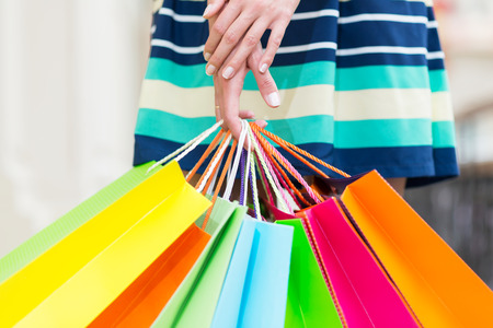 spendthrift: A lady in a skirt is holding a lot of colourful shopping bags.