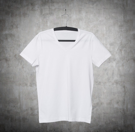 collarless: Close up of a V shape white t-shirt on cloth hanger. Concrete background.
