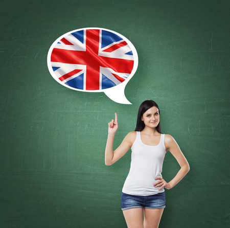 linguistics: Beautiful woman is pointing out the thought bubble with Great Britain flag. Green background.