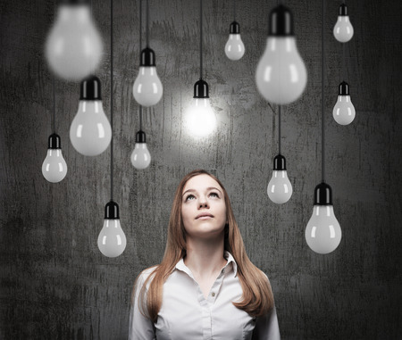 seeking an answer: Charming lady is looking upward at the hanging light bulbs. A concept of searching new ideas. Dark concrete background. Stock Photo