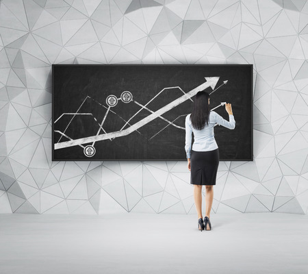 Rear view of full-length brunette woman who is presenting growing line graph on the black board. Фото со стока