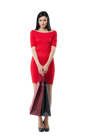retail therapy: Beautiful brunette woman in a red dress is holding fancy shopping bags. Isolated.