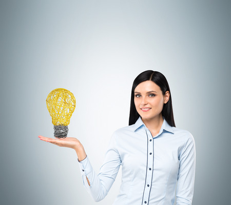 new idea: Brunette lady presents a light bulb as a concept of new idea in business.