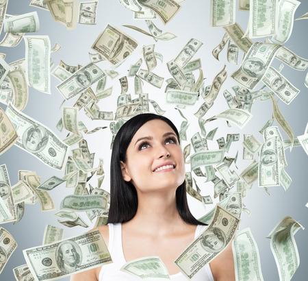 cash money: Un retrato de una mujer morena de ensue�o en una camiseta blanca. Notas del d�lar est�n cayendo desde el techo. Foto de archivo