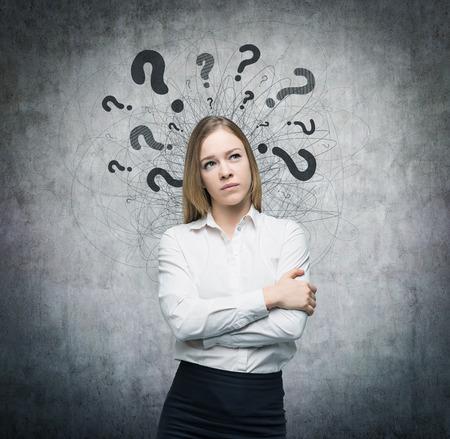 onbeantwoorde: Een portret van een mooie dame met een ondervraging meningsuiting en vraagtekens boven haar hoofd. Concrete achtergrond.