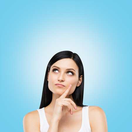 preoccupied: A portrait of a pensive brunette lady in a white tank top. Blue background.