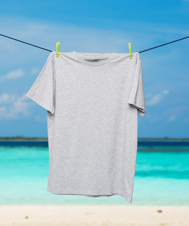 collarless: Close up of a grey t-shirt on the rope. Tropical sand beach and ocean as background.