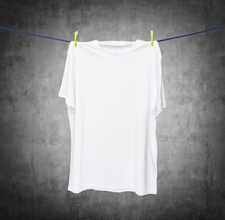 collarless: Close up of a white t-shirt on the rope. Concrete background. Stock Photo