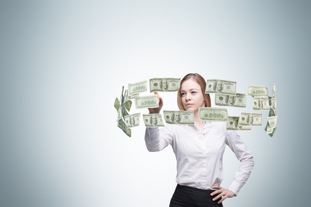 viability: Young lady is controlling cash flow of the dollar notes. Light blue background.n
