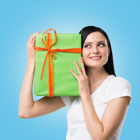 giftwrapped: A brunette woman is holding a green gift box. Blue background.