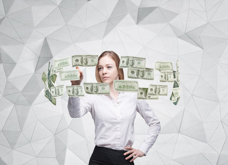 cash cycle: Young lady is controlling cash flow of the dollar notes. Contemporary background. Stock Photo