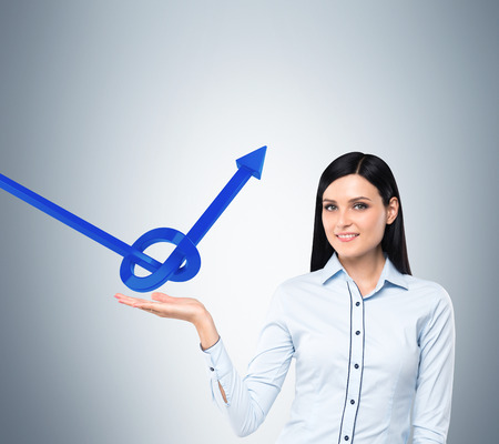 viability: Brunette business woman holds a knot from a blue arrow Stock Photo