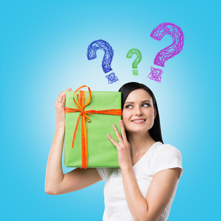 giftwrapped: A brunette woman is holding a green gift box and question mark as a concept of gift uncertainty. Blue background .
