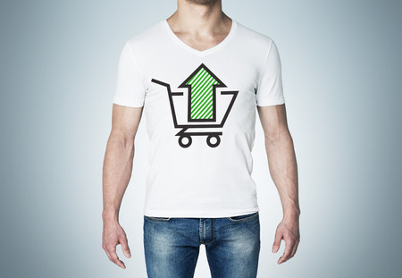 purchasing power: Close-up of a man in a white t-shirt with a sketch of the green arrow and the basket. A concept of the increasing of the purchasing power Stock Photo