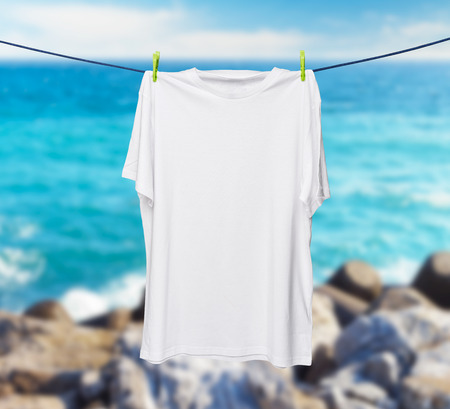 collarless: Close up of a white t-shirt on the rope. Sea and rocks in a blur as a background.
