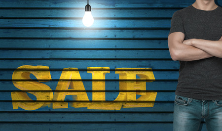 adult  body writing: Close-up of a man in a grey t-shirt with crossed hands. The word sale on the wooden wall. Stock Photo