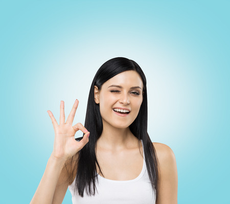 conspiratorial: Brunette woman shows ok sign. Blue background. Stock Photo