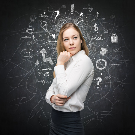 A portrait of a beautiful lady with questioning expression who is looking the best solution for the business problem. Chalk Business icons are drawn over the black chalkboard. Stock Photo