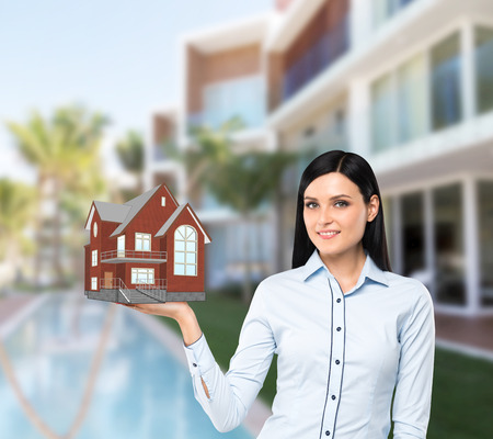 the property: Beautiful brunette property agent presents a new house for sale. Luxury villa in blur as a background.