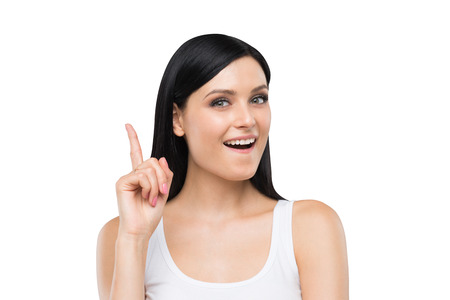 comprehension: A Portrait of an astonished brunette lady in a white tank top. Isolated.