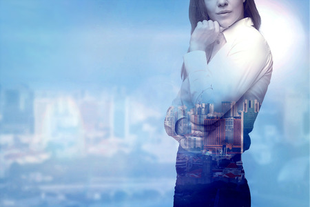 A beautiful business woman is thinking about business solutions. City view in blur as a background.