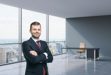 financial concept: A handsome businessman in a workplace at modern corner panoramic office in New York, Manhattan. A concept of financial consulting services.