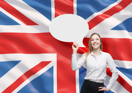 great britain flag: Beautiful woman is pointing out the empty thought bubble. Great Britain flag as a background.