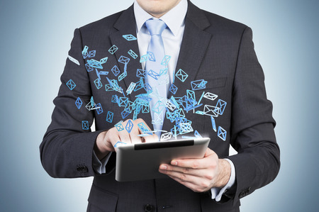 social web: Businessman is searching something in internet using a tablet. Flying social media icons.