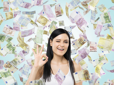 accolade: Brunette woman shows ok sign. Euro notes are falling down over blue background.