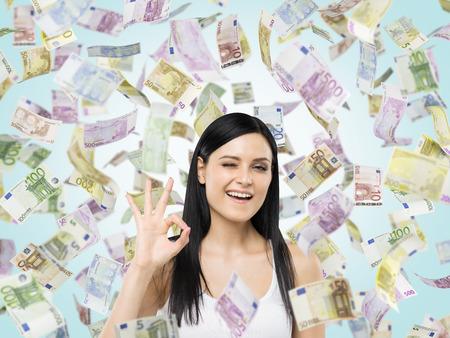 cash money: Mujer morena muestra signo ok. Billetes de euros están cayendo sobre fondo azul.