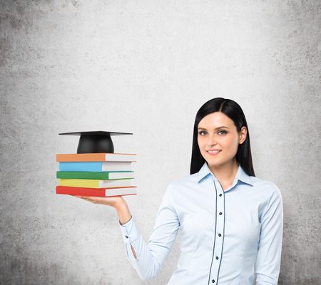 necessity: A portrait of a brunette lady with the open palm who is holding colourful books and a graduation hat. A concept of necessity of education. Concrete background.. Stock Photo