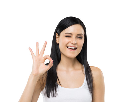 accolade: Brunette woman shows ok sign. Isolated.