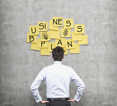 Rear view of the businessman who thinks about new business plan. Yellow stickers are hanged on the concrete wall.