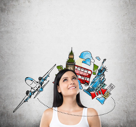 soñando: Un retrato de una mujer morena de ensueño en una camiseta blanca. Un concepto de viajes y vacaciones. Boceto viajar colorido en la pared de hormigón. Foto de archivo