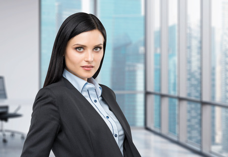 undertaker: Portrait of a beautiful brunette lady in a formal suit. Panoramic business city view from the modern office.