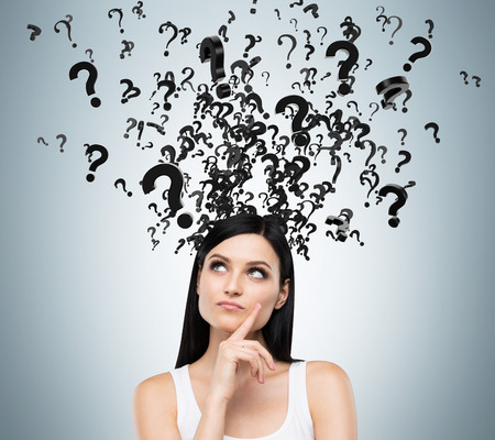 question marks: A portrait of a beautiful brunette with questioning expression and question marks above her head.