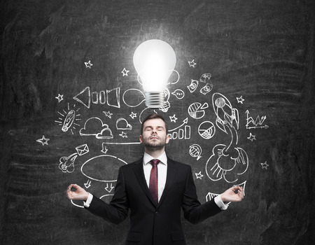 meditative: Meditative young businessman is looking for new business ideas. Drawn business icons on the black chalk board and a light bulb as a concept of new idea. Stock Photo