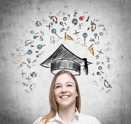 expertise concept: Young beautiful lady is thinking about studying at the university. Educational icons are drawn on the concrete wall. Stock Photo