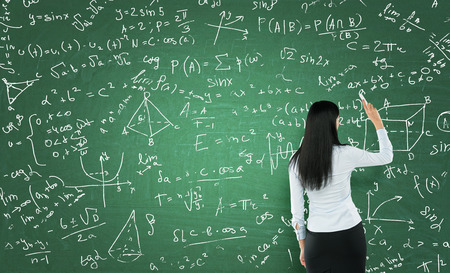 writings: Rear view of a thoughtful woman who is writing math calculations on green chalk board. Stock Photo