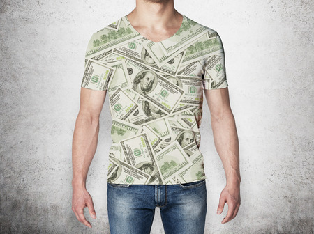 affluence: Close-up of a man in a t-shirt crafted from dollar notes. Concrete background. Stock Photo