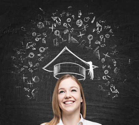 graduation hat: Young beautiful lady is thinking about studying at the university. Educational icons are drawn on the black chalk board. Stock Photo