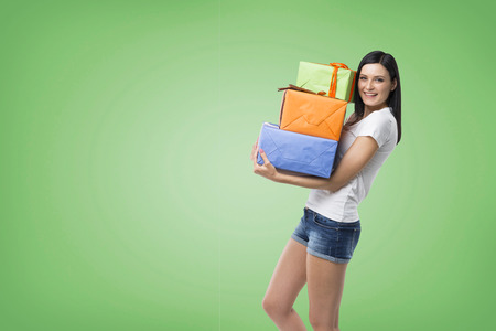 giftwrapped: A brunette woman is holding three colourful gift boxes. Green background.