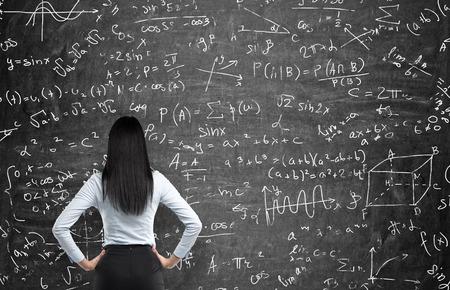 Achter mening van een doordachte vrouw die probeert om wiskundige problemen op te lossen. Wiskundige berekeningen op zwart krijt bord. Stockfoto
