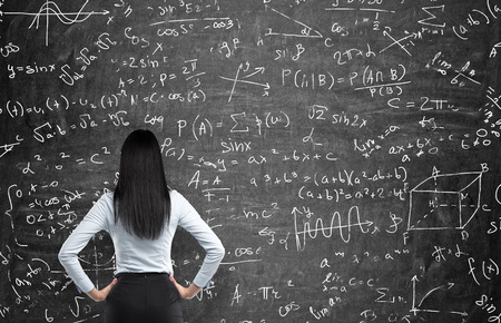 calculations: Rear view of a thoughtful woman who tries to solve math problems. Math calculations on black chalk board. Stock Photo
