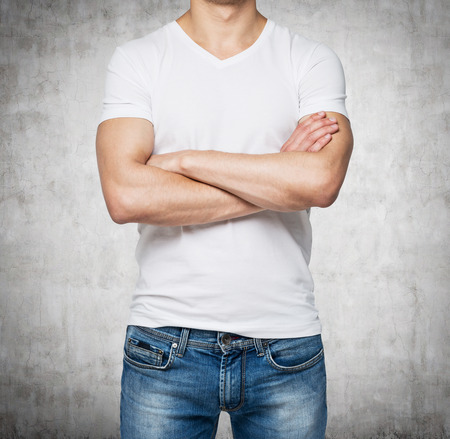 v shape: Front view of a person in a white V shape t-shirt with crossed hands. Concrete wall on background. Stock Photo