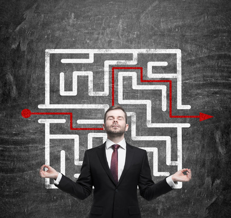 inventive: Meditative businessman and solved labyrinth with a red arrow on the black chalk board.