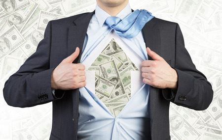 affluence: Businessman is tearing the shirt on the chest. Dollar notes under the shirt. The concept of the business soul. Dollar notes background.