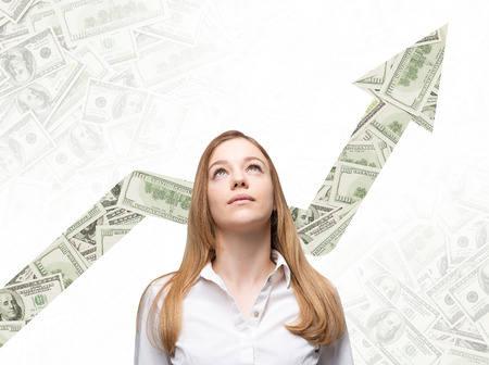 dollar: A business woman is looking up and thinking how to increase return of the business process. Increasing arrow which is made of dollar notes on the background.