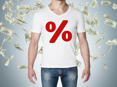 paper money: Close up of the body view of the man in a white t-shirt with the red percentage sign on the chest. Concept of the sale. Falling dollar notes over blue background. Stock Photo