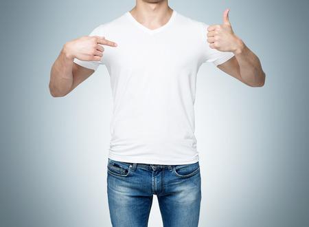 the shirt: Primer plano de un hombre apuntando con su dedo a una camiseta en blanco y el pulgar hacia arriba. Fondo azul.